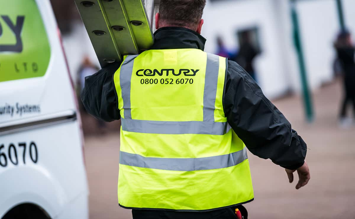 Security engineer carrying ladders